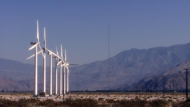 Windmills turn in the eerily misted California desert.