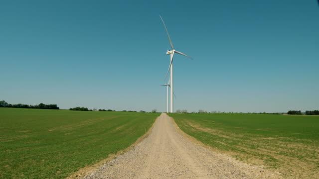Windmills / wind turbines on field with gravel road