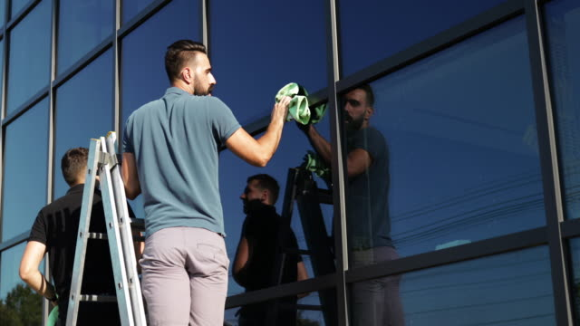 window cleaners working together - lavare video stock e b–roll