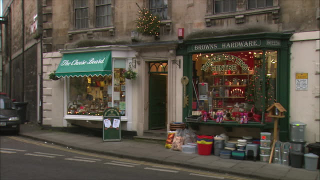 vídeos de stock, filmes e b-roll de ws window display of key cutting center and store with christmastime decorations / bradford on avon, wiltshire, united kingdom - loja de conveniência