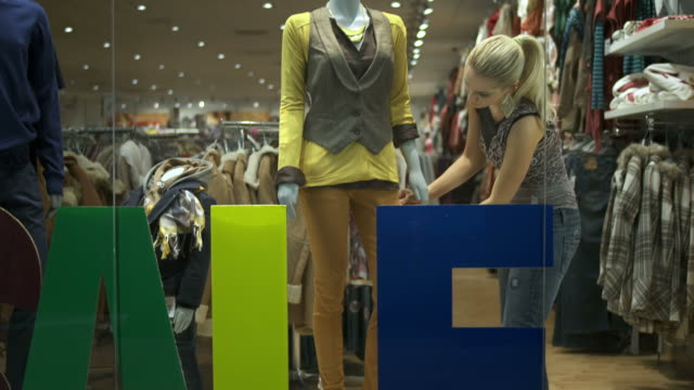 hd dolly: window dresser adjusting clothes on mannequin - clothing store stock videos and b-roll footage