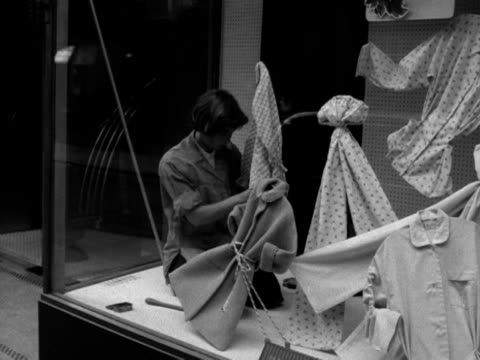a window dresser works on a display in a shop window 1956 - bluse stock-videos und b-roll-filmmaterial