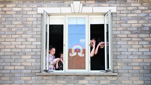 window family portrait at home and rainbow symbol - neighbour stock videos & royalty-free footage
