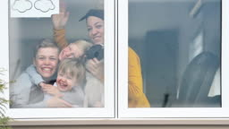 Window family portrait at home with pet dog and rainbow symbol