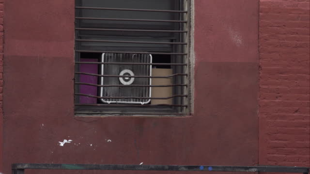 window fan runs on a hot day in brooklyn. - security bar stock videos and b-roll footage