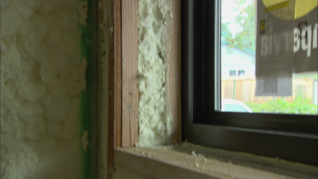 cu tu td window frame under construction where insulation has just been blown in and is exposed / portland, oregon, usa - isoliermaterial stock-videos und b-roll-filmmaterial