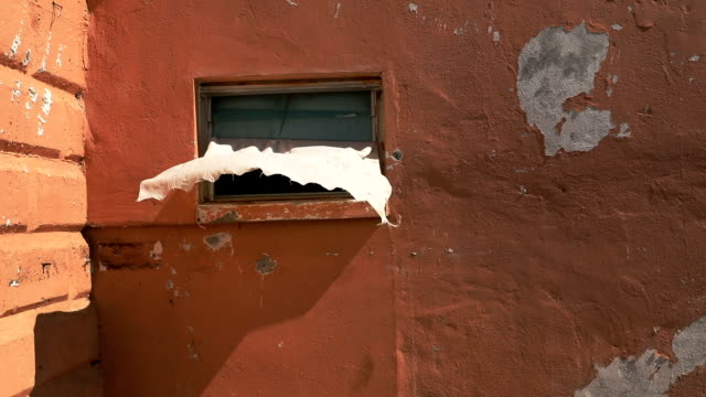 A window is half open from a destroyed property on the island of Barbuda on December 8 2017 in Cordington Barbuda Barbuda which covers only 62 square...