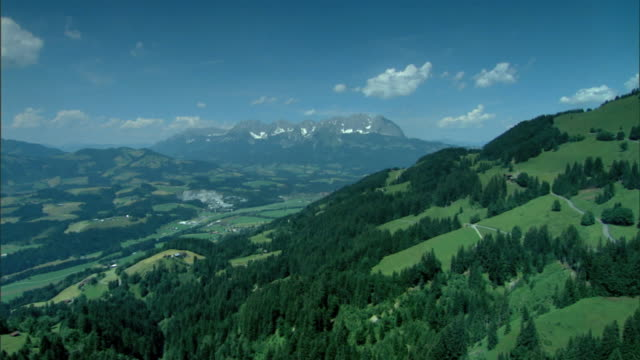 ws grassy mountainside patches of evergreen trees valley larger mountains bg excursion sightseeing holiday vacation - austria video stock e b–roll