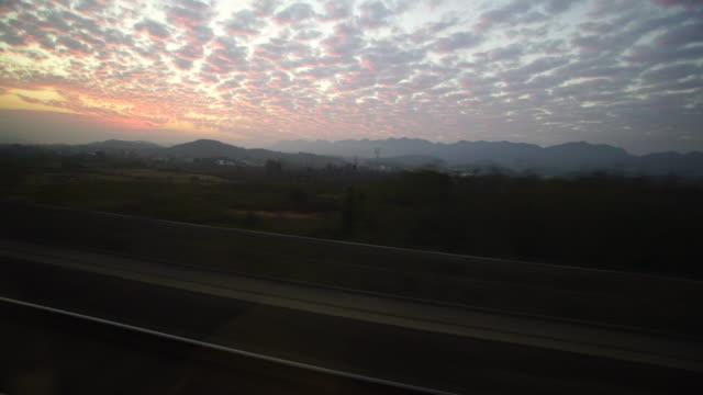 vidéos et rushes de window outside of train travel in dusk after sunset in china - scène rurale