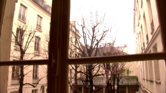 a window overlooks a small courtyard where children play. - atrium grundstück stock-videos und b-roll-filmmaterial