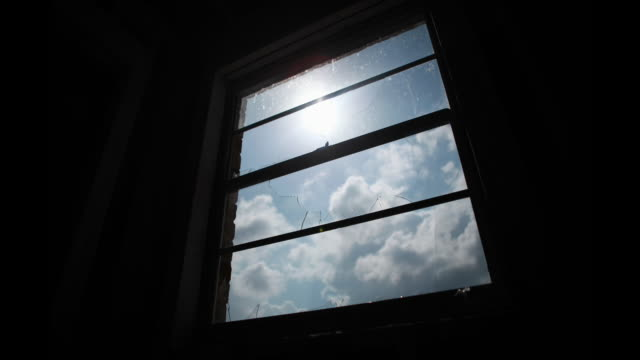 A window pane frames a bright sun and passing clouds.
