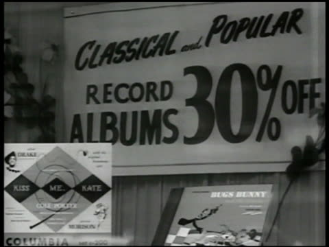 Window shoppers 'Dynamic' records store CU Sign '30% off' INT MS Customers shopping in record store VS Girl in booth listening to record CU Record...