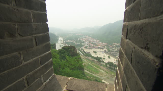 window view captures the surrounding landscape from the great wall of china. - surrounding wall stock-videos und b-roll-filmmaterial