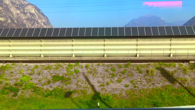 Window View from a Train over a Street with Solar Panels and Mountain in a Sunny day