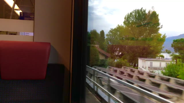 Window View From a Train over Alpine Lake Maggiore with Houses and Mountain