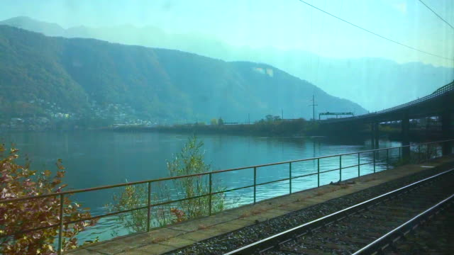 Window View from a Train over an Alpine Lake with Mountain and under a Bridge in a Sunny Day