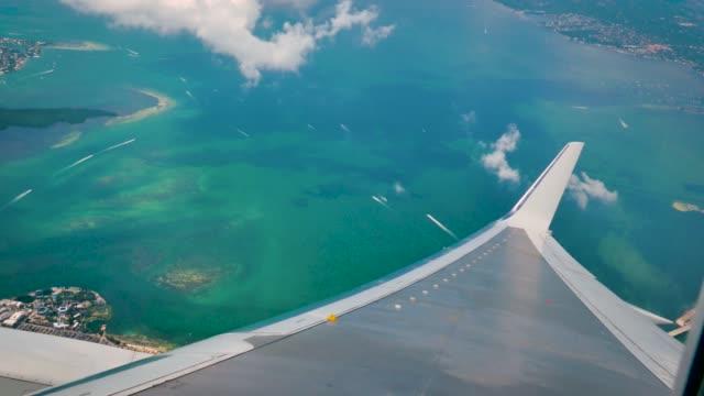 fenster mit blick auf ein flugzeug über miami bereich mit meer und cays - miami stock-videos und b-roll-filmmaterial