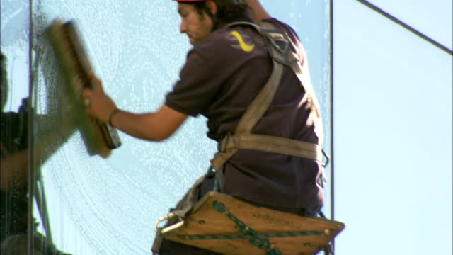 a window washer cleaning a skyscraper in a harness available in hd. - window washer stock videos & royalty-free footage