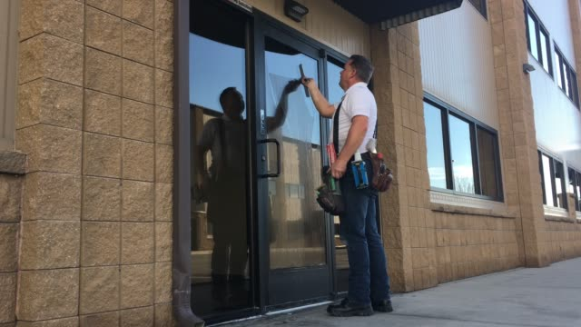 window washer cleans building doors - tool belt stock videos and b-roll footage