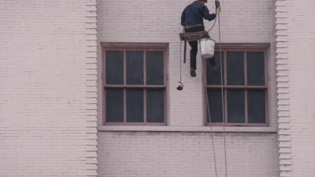 a window washer lowers himself to a high-rise window and begins cleaning. - window washer stock videos & royalty-free footage
