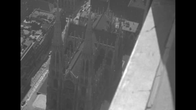 window washers clean the outer windows of a skyscraper in new york city / tiltdown shot window washer strapped to the outside of the building waves... - st. patrick's cathedral manhattan stock videos and b-roll footage