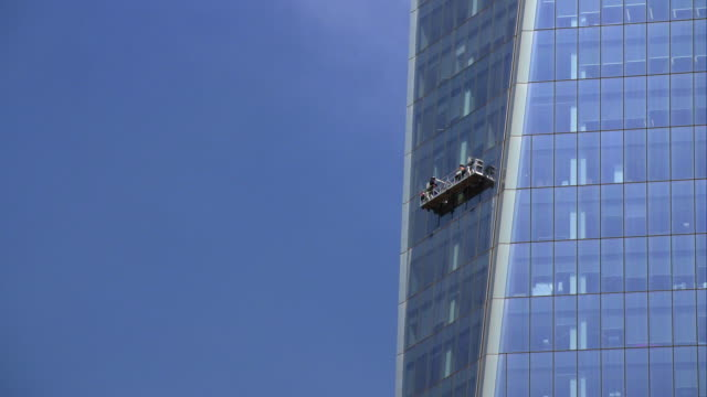 window washers clean the side of the world trade center building on a clear day. - window washer stock videos & royalty-free footage