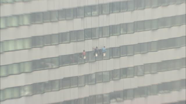 ws ha zo window washers scrubbing side of building, beijing, beijing, china - window washer stock videos & royalty-free footage