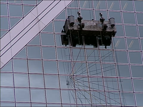 ews la window washing rig on side of the bank of china tower in hong kong, zoom in tilt up ws as the rig moves upward, zoom out. - bank of china tower hong kong stock videos & royalty-free footage