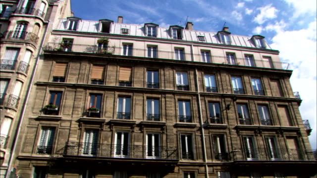 windows and balconies cover the facade of a large multistory building in paris. - paris france stock videos & royalty-free footage