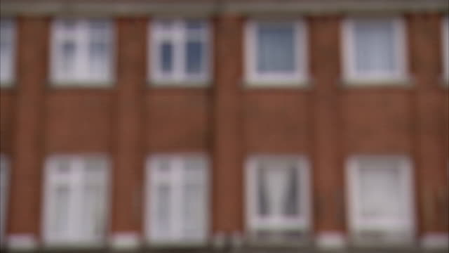 Windows closely line a brick apartment building in London. Available in HD.