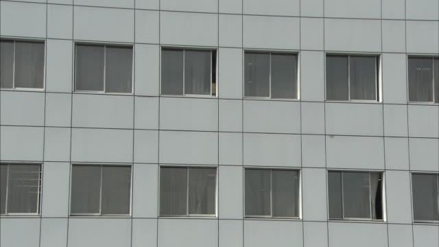 vidéos et rushes de windows line a facade of the national cerebral and cardiovascular center at osaka. - facade