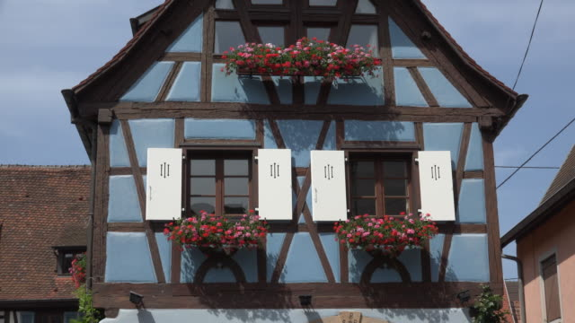 Windows with geranium in half-timbered house in a picturesque village