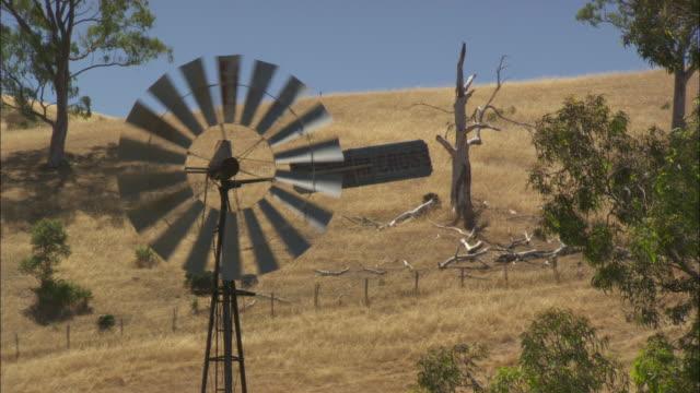 A windpump turns in the Australian countryside.