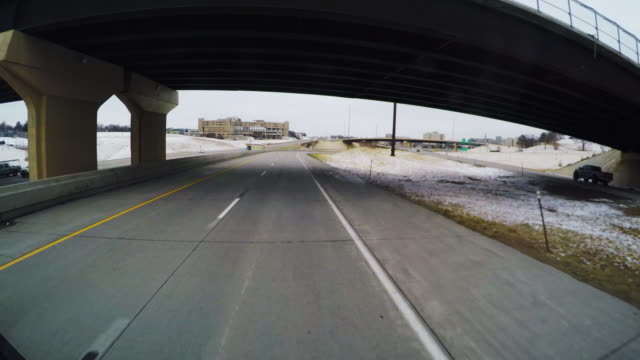 pov of windshield automobile, truck, or bus; speeding north on i-480 toward omaha in the winter; travel under several overpasses. - autostrada interstatale americana video stock e b–roll