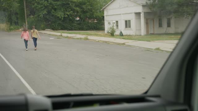 vídeos de stock, filmes e b-roll de windshield of van stalking girls walking on neighborhood street / pleasant grove, utah, united states - espreitando