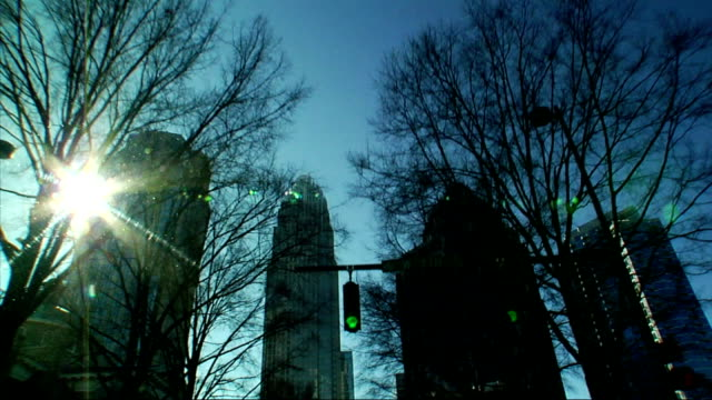 driving southwest down south tyron street in uptown charlotte sunny day w/ blue sky passing bare trees skyscrapers traffic lights approaching bank of... - bank of america stock videos & royalty-free footage