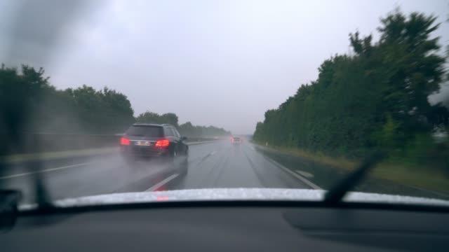 vidéos et rushes de ms essuie-glaces de compensation de pluie hors voiture de conduite le long de l'autoroute - condition