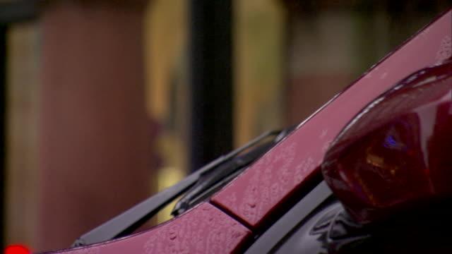 windshield wipers moving on red vehicle, rain, soft focus & one unidentifiable pedestrian bg, car moves slightly, drives away. raining, urban, city,... - softfokus bildbanksvideor och videomaterial från bakom kulisserna