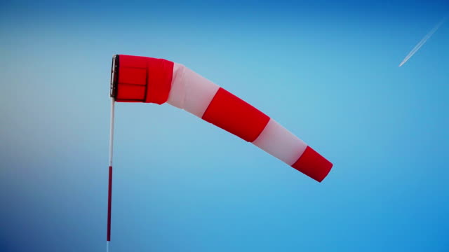 Windsock against blue sky and airplane
