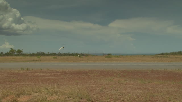 windsock and blue sky at maningrida, nt, australia - airfield stock videos & royalty-free footage