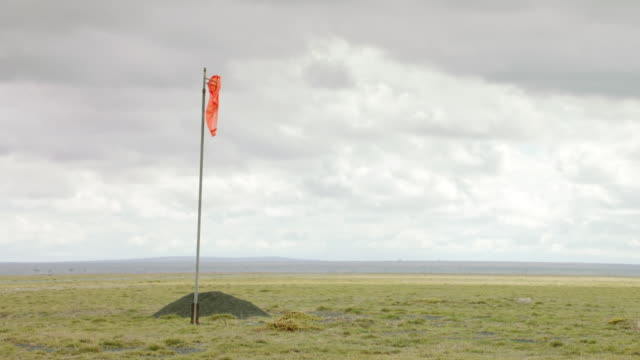 vídeos de stock, filmes e b-roll de ws pan windsock on savanna landscape / kenya - biruta