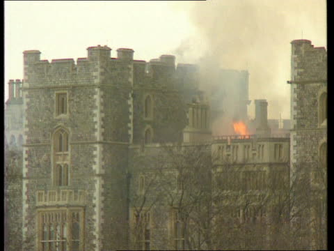 berkshire windsor ext gv castle with smoke rising and fire engines around cms flames above battlements cms smoke and flame from turret window la lms... - windsor england stock videos and b-roll footage