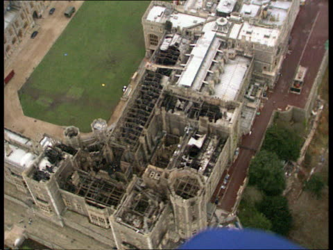 speculation on cause and cost of repairs; d)naf: england: windsor castle airv damage to roof of castle seen track r-l tx.23.11.92/naf - repairing stock videos & royalty-free footage