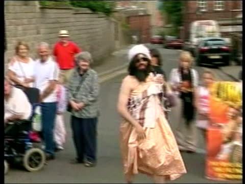 report lib aaron barschak towards past onlookers wearing fancy dress outfit as shouting 'happy birthday' lifting skirt to show beard on crotch cars... - pelvi video stock e b–roll