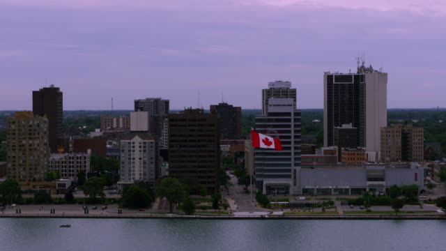 windsor ontario canada waterfront aerial - bandiera del canada video stock e b–roll