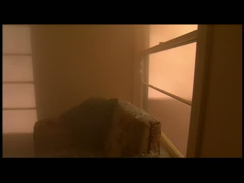 Windstorm breaking window, blowing dust into room