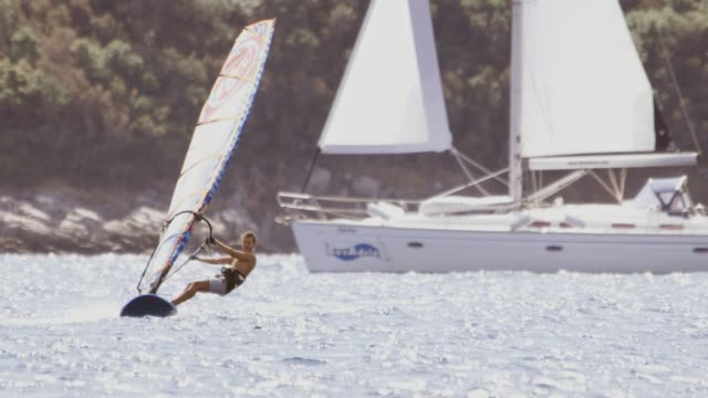slo mo windsurfer against a sailboat - water sports equipment stock videos and b-roll footage