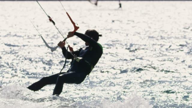 stockvideo's en b-roll-footage met slo mo windsurfer en kitesurfer surfen op de oceaan - windsurfen
