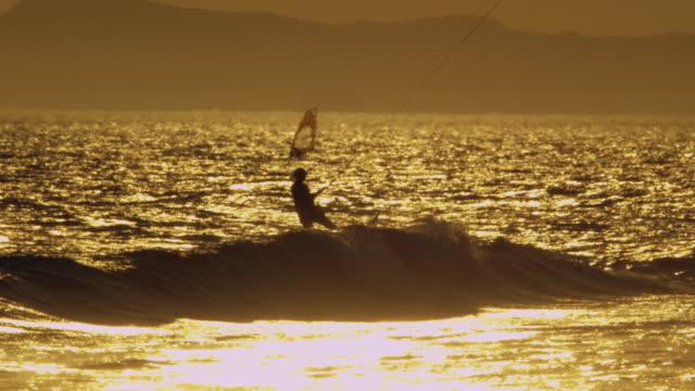 stockvideo's en b-roll-footage met windsurfer and kitesurfers backlit on sunset - windsurfen