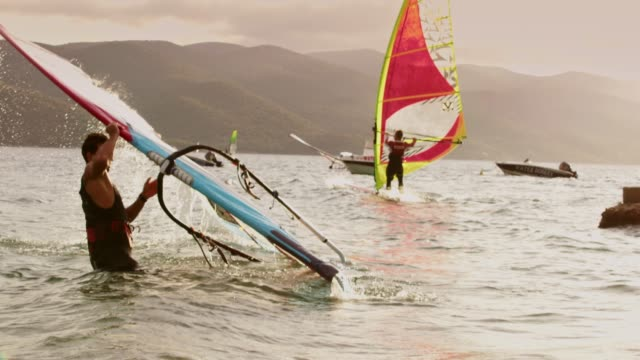 slo mo windsurfer carrying a sail - carrying stock videos & royalty-free footage